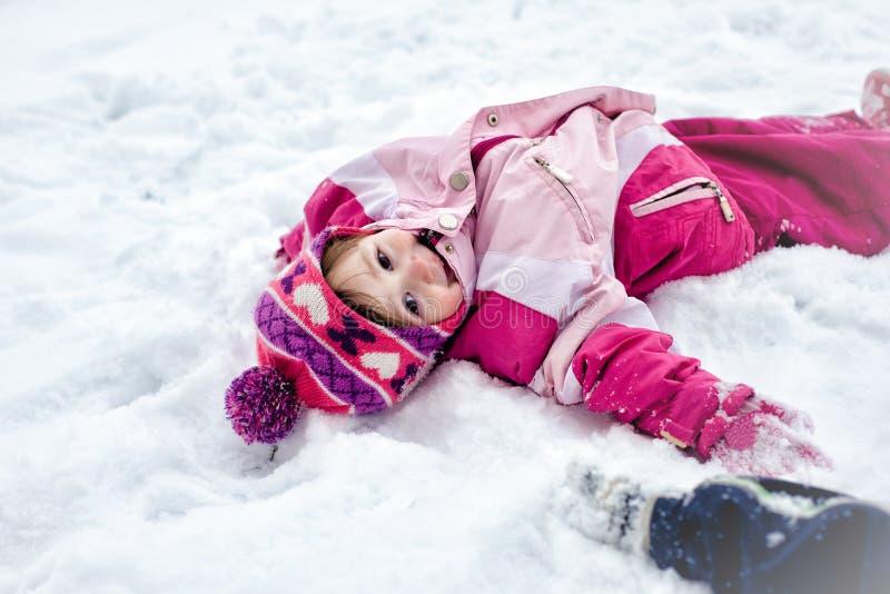 La petite fille mignonne se trouvant dessus soutiennent dans la neige photo libre de droits
