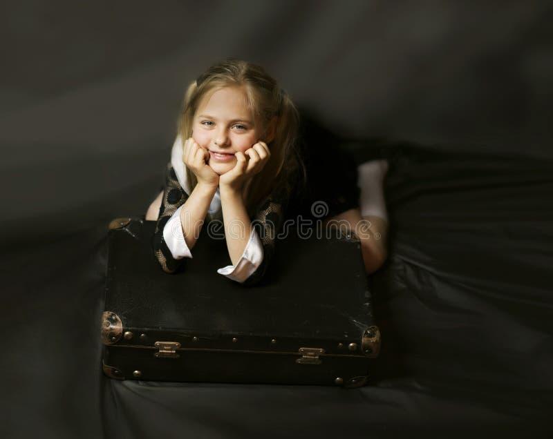 La petite fille mignonne se trouve sur une vieille valise minable photos libres de droits