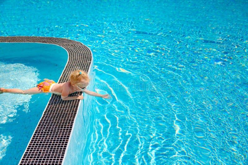 La petite fille mignonne, touchant l'eau dans la piscine photos libres de droits