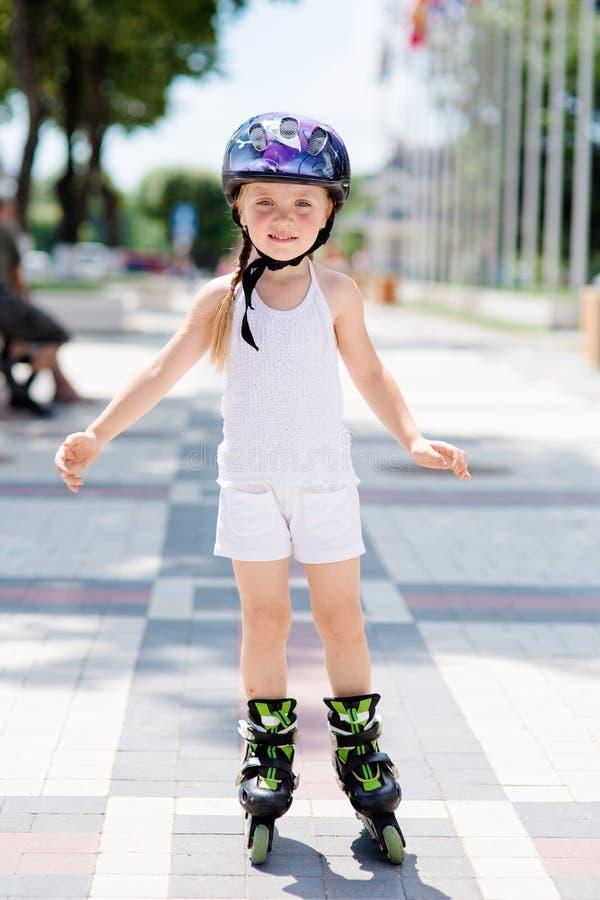 La petite fille monte sur des patins de rouleau au parc photographie stock libre de droits