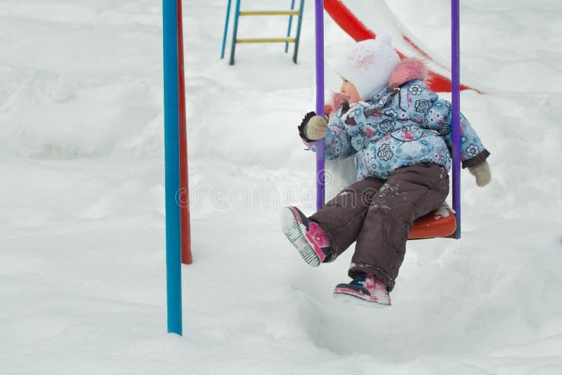La petite fille monte sur la bâche givrée d'oscillation de terrains de jeu d'hiver avec la neige blanche dehors images stock