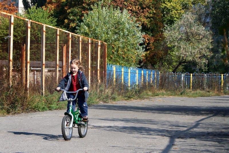 La petite fille monte un vélo images stock