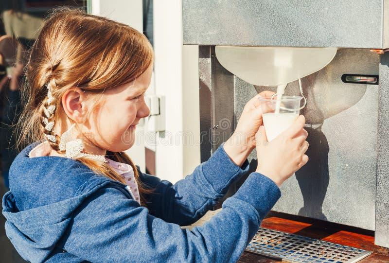 La petite fille obtient le lait de la machine à une ferme photos libres de droits