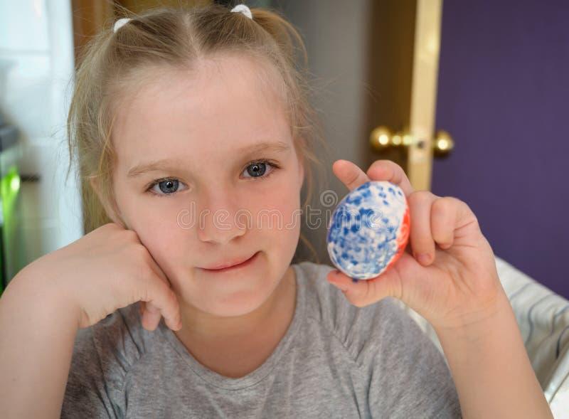 La petite fille peint l'oeuf de pâques à la maison photo libre de droits