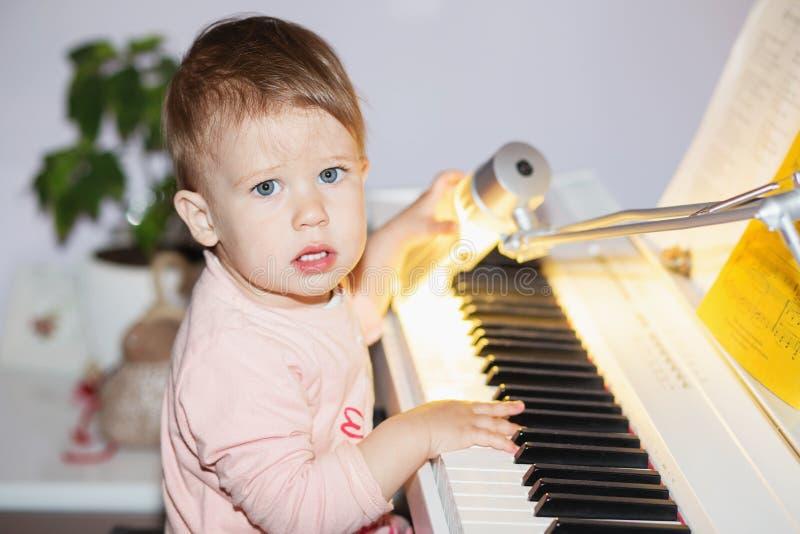 La petite fille a plaisir à jouer le synthétiseur électrique de piano pour le f images libres de droits