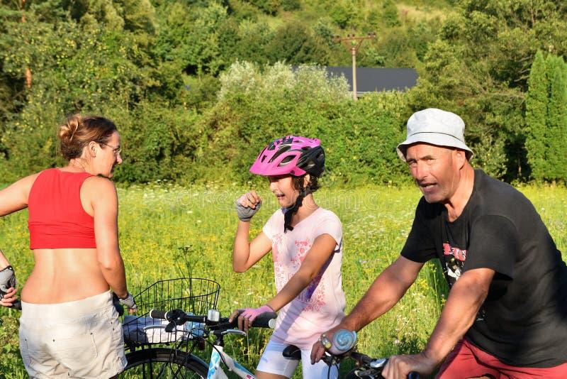 La petite fille pleure pendant faire du vélo sur la route avec le parent image libre de droits
