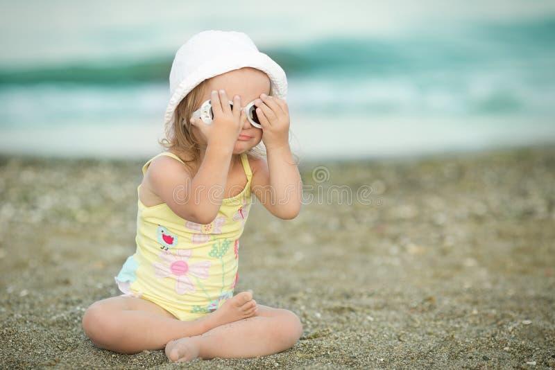 La petite fille porte des lunettes à la plage photo stock