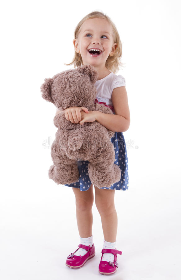 La petite fille porte un ours de nounours photo stock
