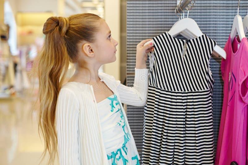 La petite fille prend le cintre avec la robe du support photos stock