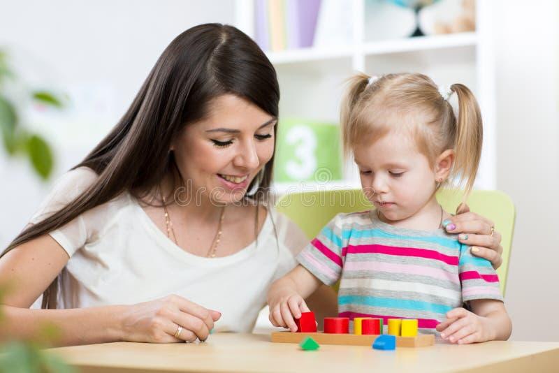 La petite fille résout le puzzle Mère observant à ses actions image libre de droits