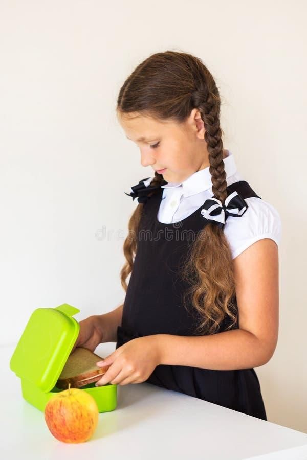 La petite fille rassemble le déjeuner pour l'école dans la cuisine photos libres de droits