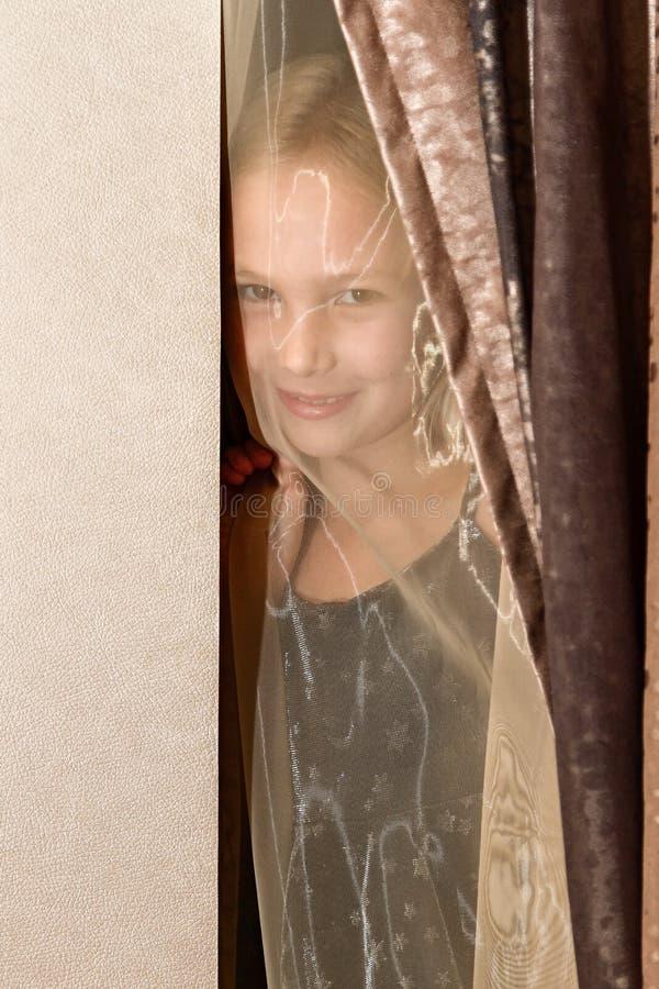 La petite fille regarde en raison des rideaux images stock