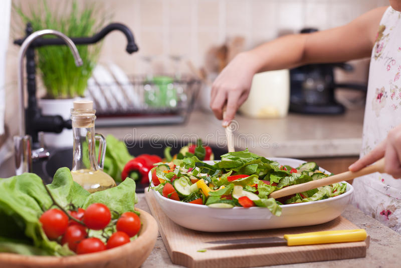 La petite fille remet mélanger les légumes coupés dans une salade, SH photo libre de droits