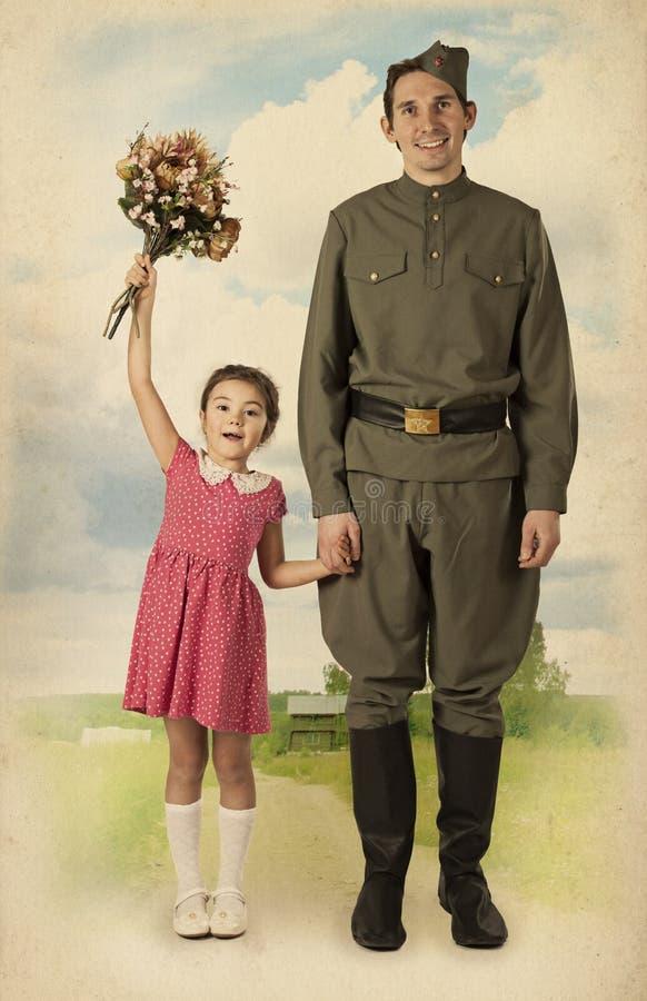La petite fille rencontre un soldat photo stock