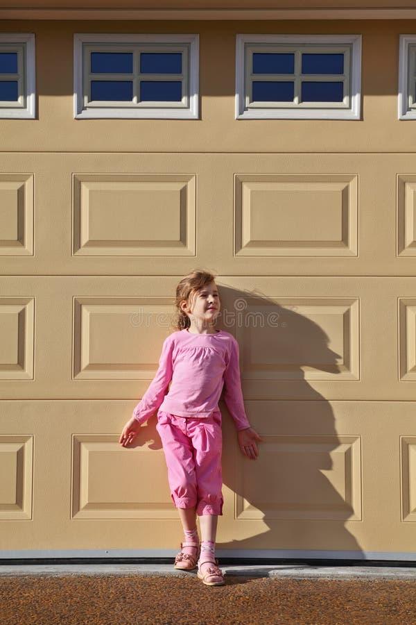 La petite fille reste le mur proche image stock