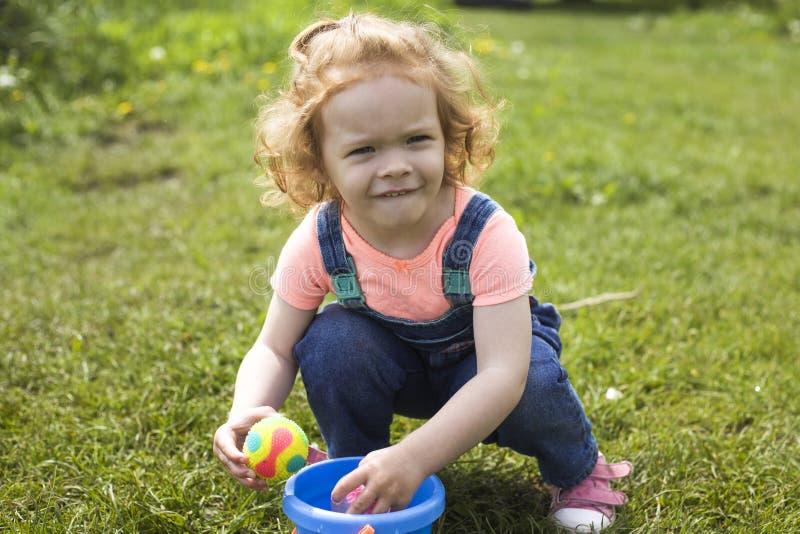 La petite fille rousse joue sur la pelouse et serre ses yeux du soleil lumineux photos stock