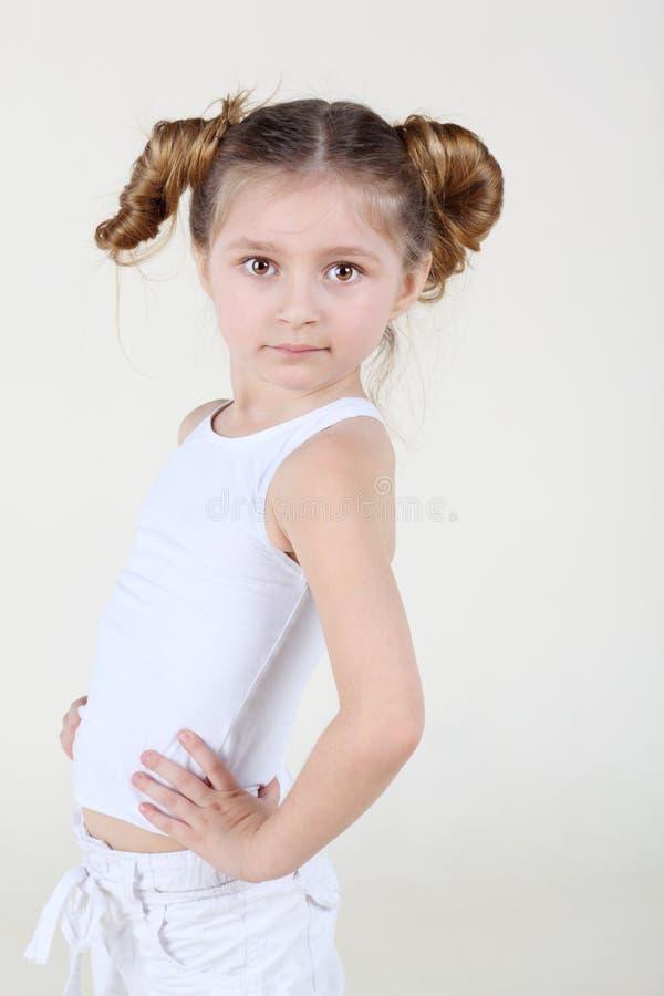 La petite fille sérieuse reste et garde des mains à la taille photographie stock