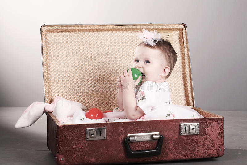 La petite fille s'assied dans une valise. photographie stock