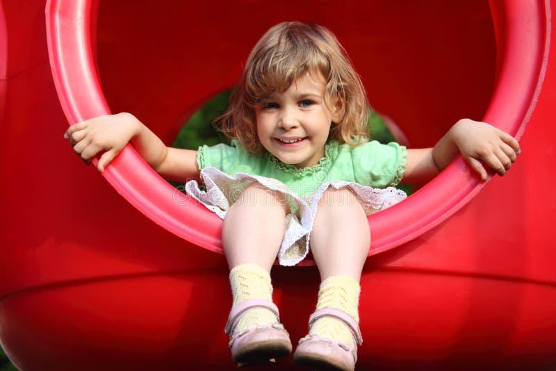 La petite fille s'assied en trou en plastique sur la cour de jeu photo stock