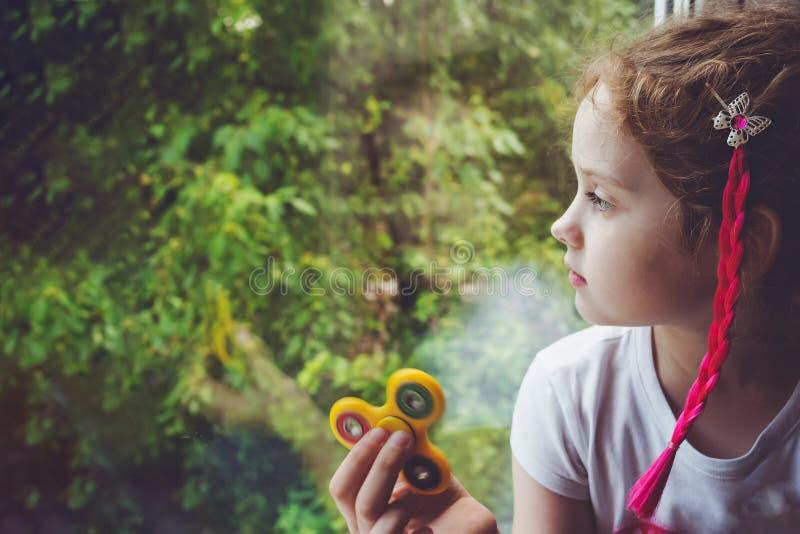 La petite fille s'assied par la fenêtre et joue un fileur photos libres de droits