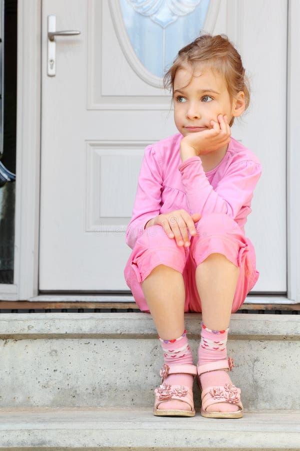 La petite fille s'assied sur des escaliers près de la trappe photographie stock libre de droits