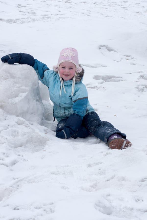 La petite fille s'assied sur la neige images stock