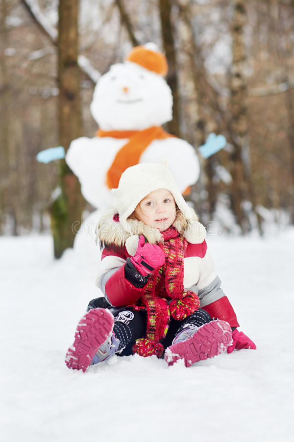 La petite fille s'assied sur la neige devant le grand bonhomme de neige images stock