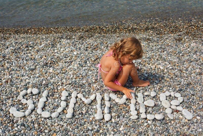 La petite fille s'assied sur la plage près pour arroser. photos stock