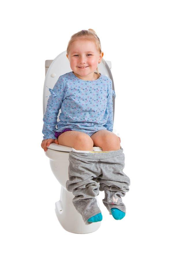 La petite fille s'assied sur la toilette images libres de droits