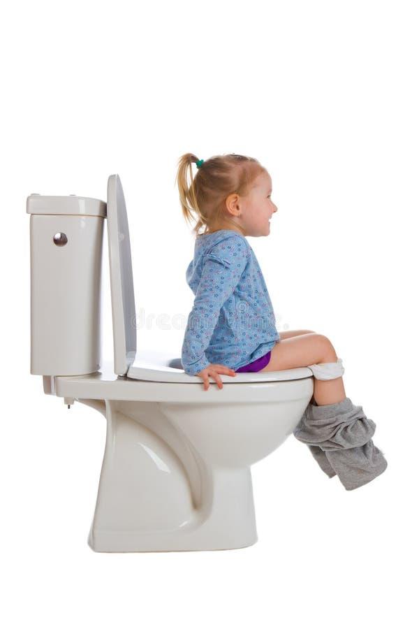 La petite fille s'assied sur la toilette photographie stock libre de droits