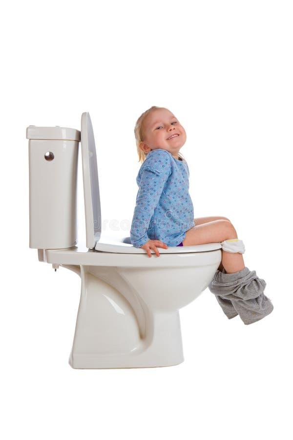 La petite fille s'assied sur la toilette photographie stock