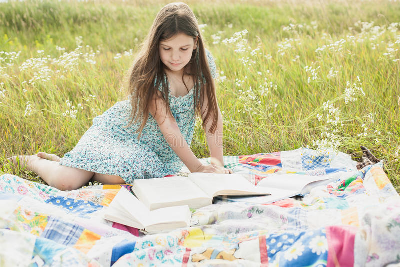 La petite fille s'assied sur le champ et lit des livres photos stock