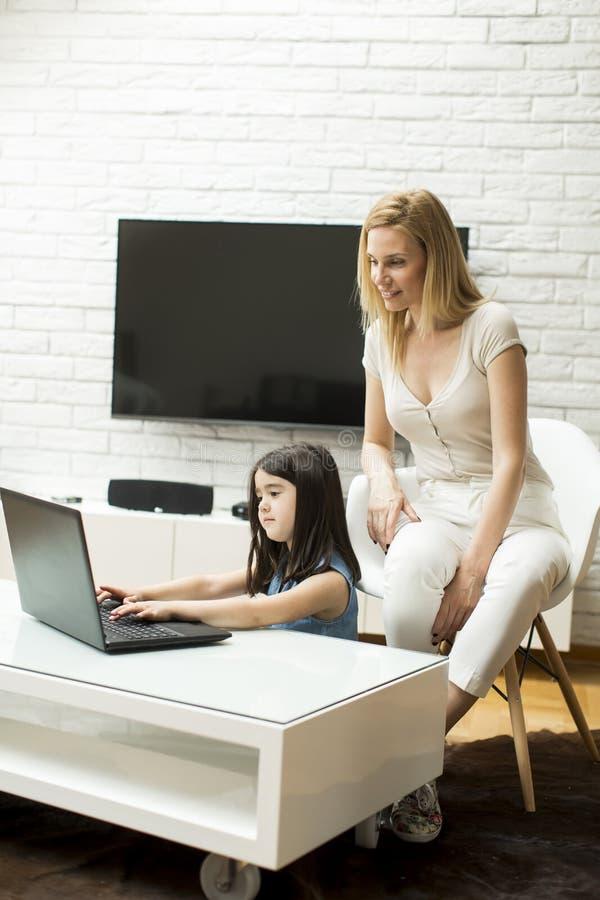 La petite fille s'assied sur le plancher et utilise un ordinateur portable photographie stock libre de droits