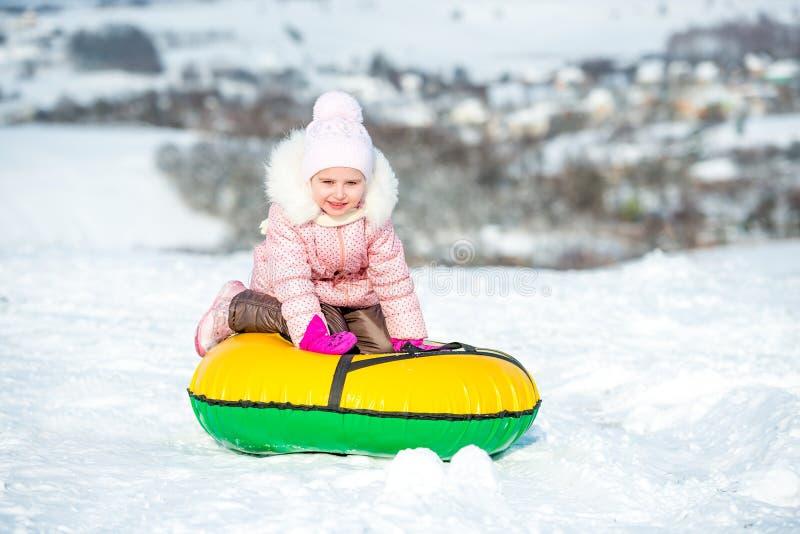 La petite fille s'assied sur le tube de neige photos libres de droits