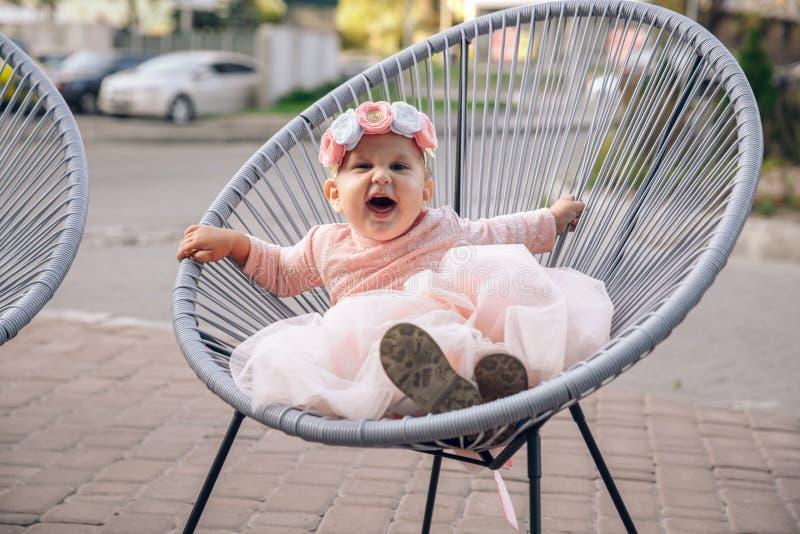 La petite fille s'assied sur un fauteuil extérieur photo libre de droits