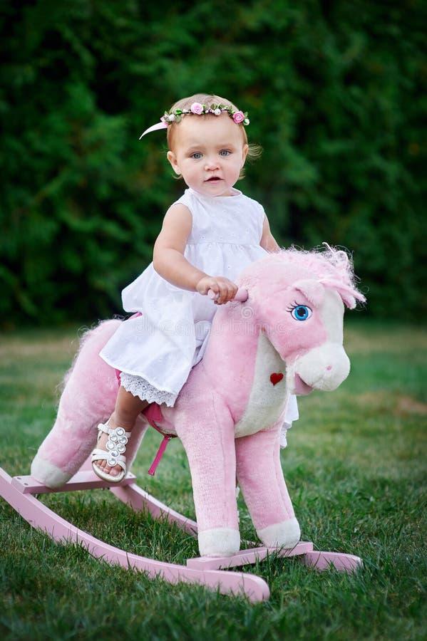 La petite fille s'est habillée comme cow-girl jouant avec le cheval de jouet en parc photo stock
