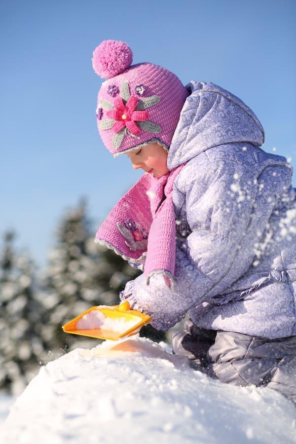 La petite fille s'est habillée dans des fouilles chaudes de vêtements avec la pelle et s'assied photographie stock