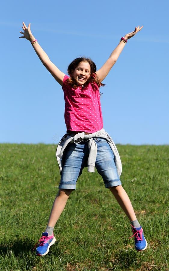 La petite fille saute sur la pelouse photographie stock