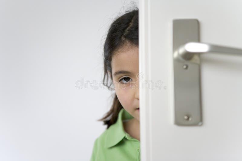 La petite fille se cache derrière la trappe images libres de droits