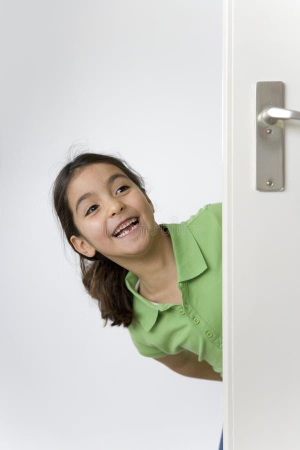 La petite fille se cache derrière la trappe pour l'amusement photographie stock libre de droits