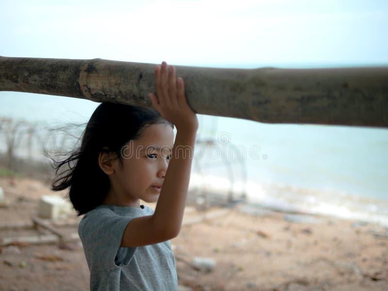 La petite fille se tenant prêt la balustrade de guidon par la mer Fille asiatique regardant en avant la plage photo stock