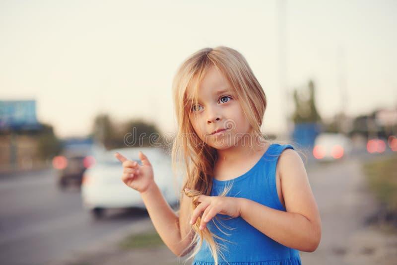 La petite fille se tient à la route photo stock