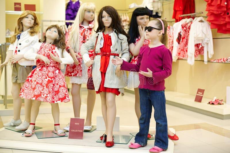 La petite fille se tient ainsi que le groupe de mannequins photo stock