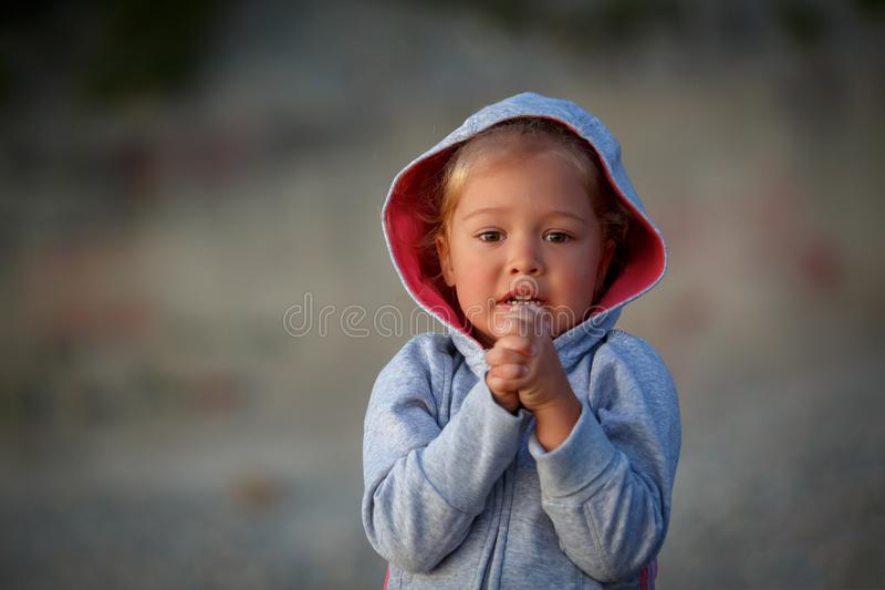 La petite fille se tient avec ses mains étreintes et prie d'accomplir son désir photo libre de droits