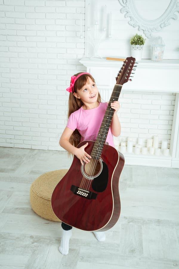 La petite fille se tient avec une guitare photographie stock libre de droits