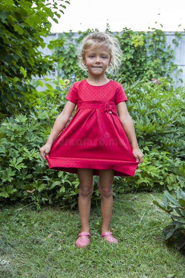 la petite fille se tient dans l'arrière-cour dans une robe rouge et répand le Th photographie stock