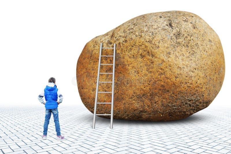La petite fille se tient devant un proche en pierre énorme qui il y a une échelle photos stock