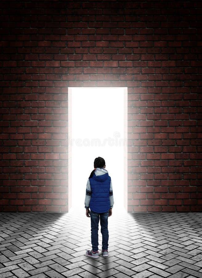 La petite fille se tient devant une porte dans un mur derrière lequel une lumière blanche lumineuse photos stock
