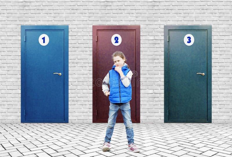La petite fille se tient près d'un haut mur de briques en lequel trois portes avec différents nombres photo stock