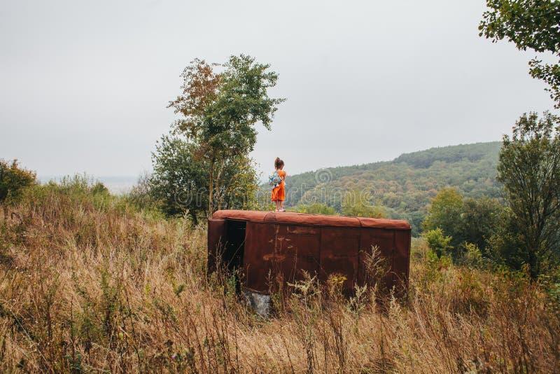 La petite fille se tient sur la vieille remorque dans les bois photos stock